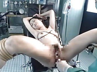 The crazy doc got this brunette cutie tied on the gynecologist table and began his experiments. She stood there with her legs spread and tied while he