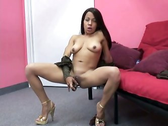 Ravishing dark skinned babe is all naked displays her soaking wet shaved pussy. She pokes her cooch with dildo and fondles her big clit.