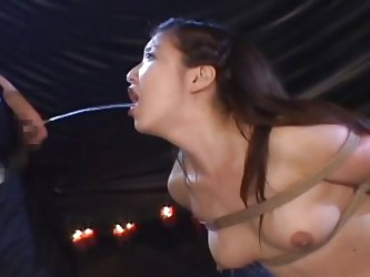 This Asian slut is tied up in rope in the sex dungeon of her master. He pulls out his pathetic dick and pisses straight into her open mouth. She swall