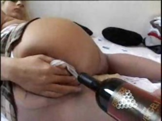 Drunken chick fucks her pussy with a bottle